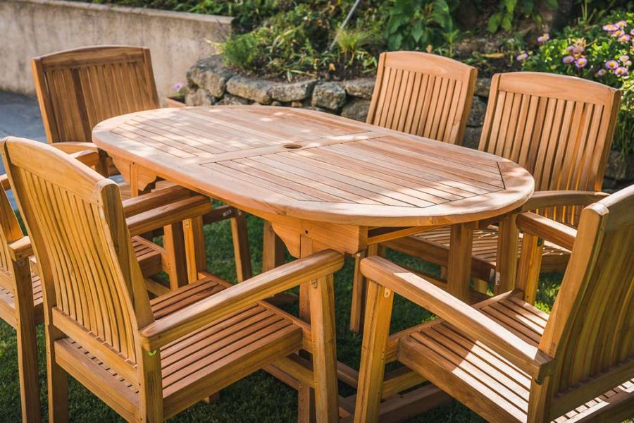 Teak Fixed Oval pedestal table With 6 stacking Charlotte chairs